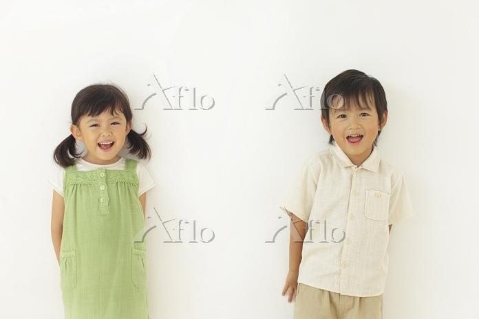 白い壁の前に立つ男の子と女の子