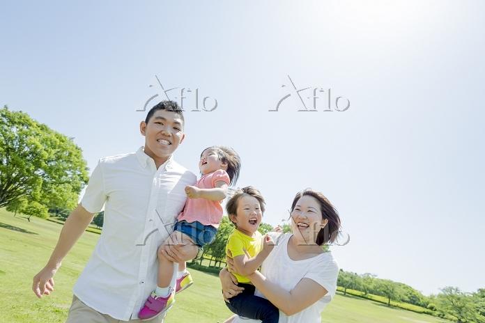 新緑の公園で遊ぶ日本人家族