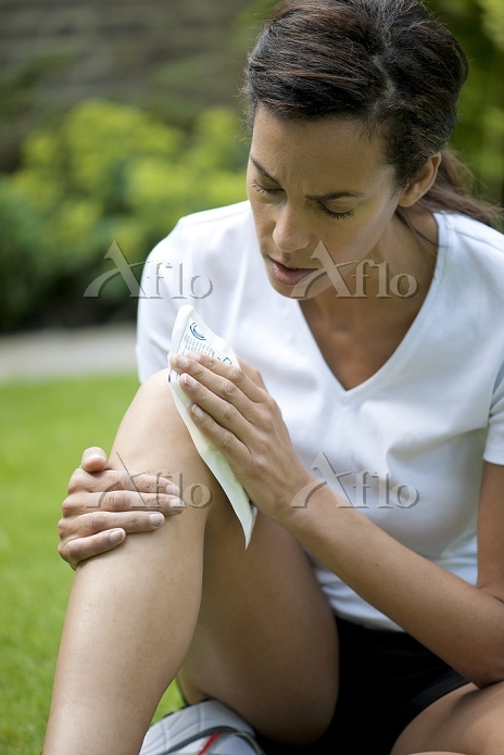 Woman applying an ice pack to ・・・