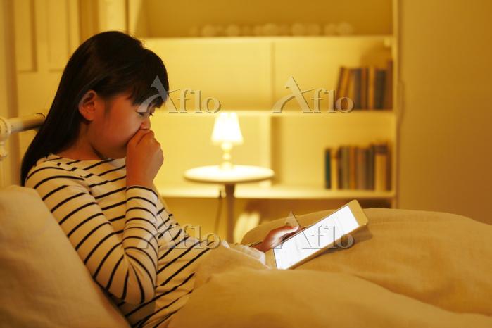 ベッドでタブレットを操作する日本人の女の子