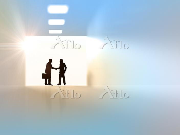 握手するビジネスマンのシルエット背景