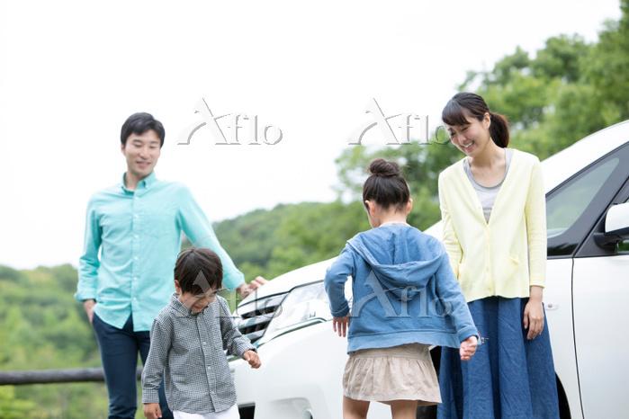 車の前で遊ぶ日本人家族
