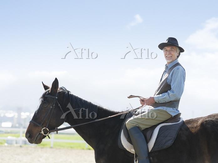 馬に乗るシニアの日本人男性