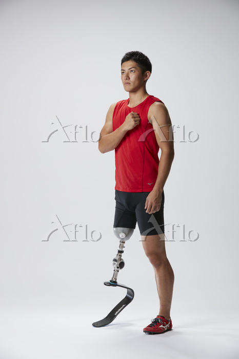 胸に手を当てる義足陸上競技選手
