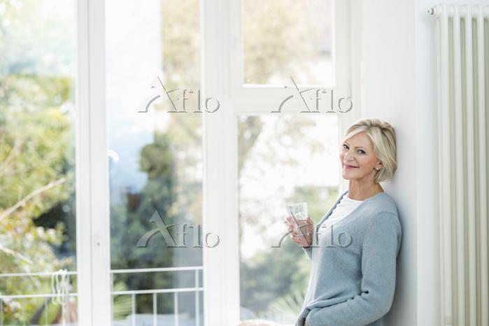 窓辺で水を持つシニア女性