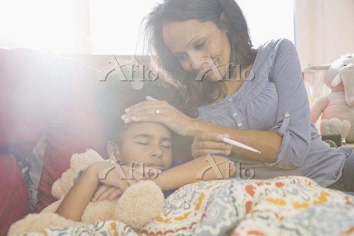 風邪の子供を介抱する母親