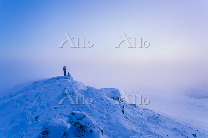 Man and dog hiking on top of s・・・
