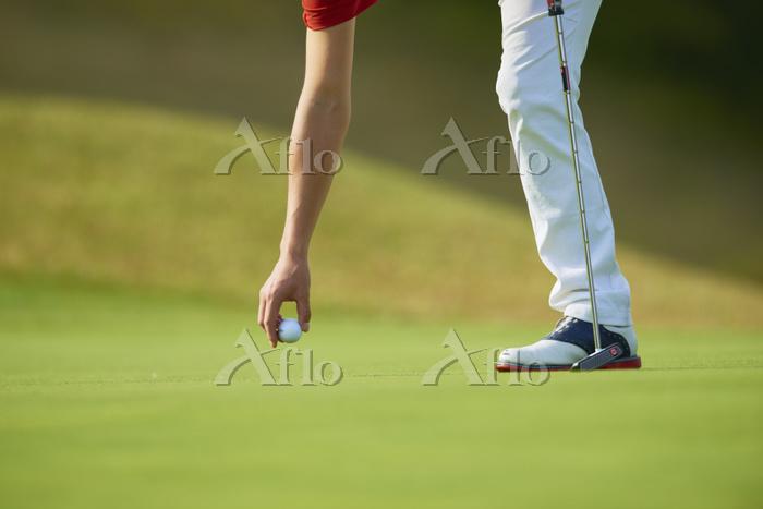 パターショットの準備をする男子ゴルフ選手