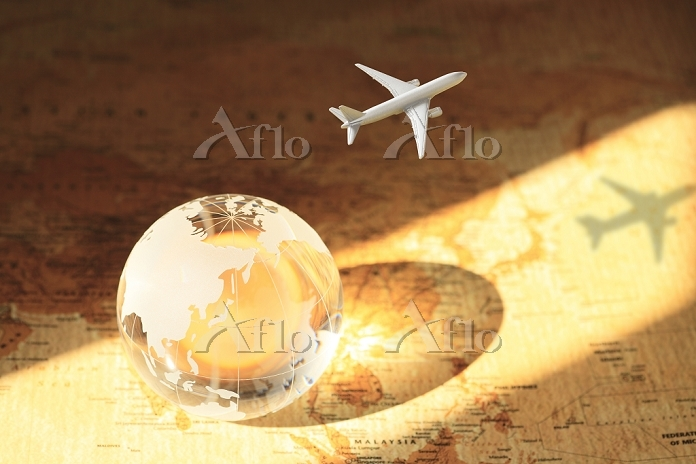 世界地図の上に置かれたクリスタル地球儀とミニチュアの飛行機