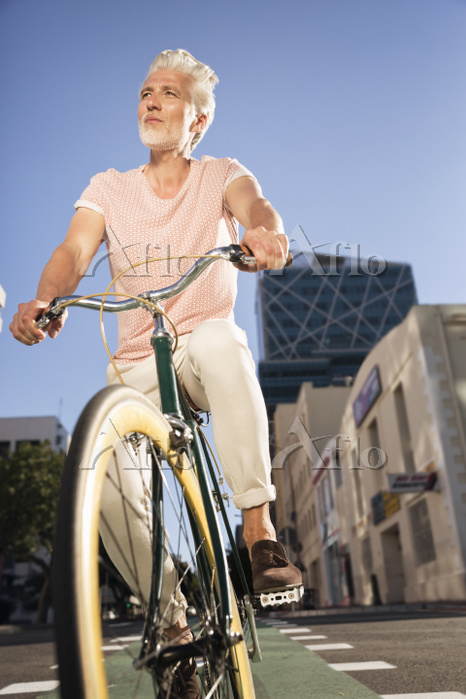 Mature man riding bicycle in t・・・