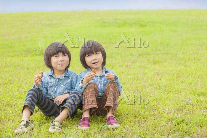 草原に座りお菓子を食べる双子の兄弟
