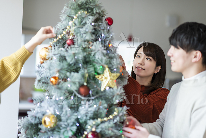 クリスマスツリーに飾り付けをする日本人の若者