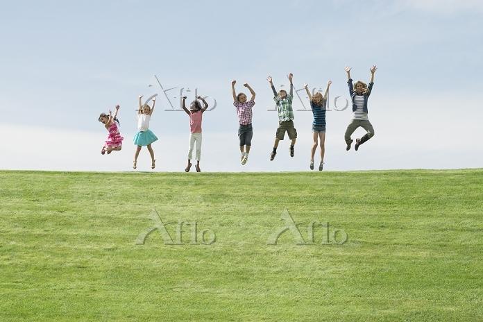 丘の上でジャンプをする子供たち