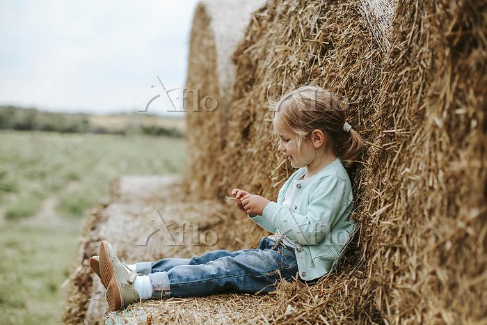 Little girl sitting on straw b・・・