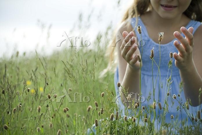 蝶をつかまえようとする女の子