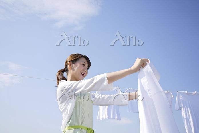 青空の下で家族の洗濯物を干す日本人女性
