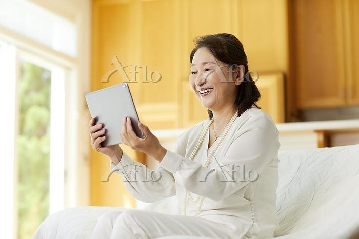 タブレットを操作する日本人シニア女性