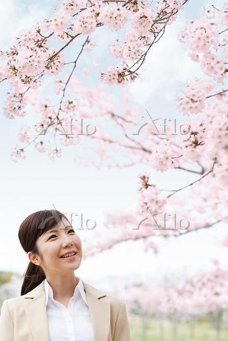 桜を眺めるビジネスウーマン