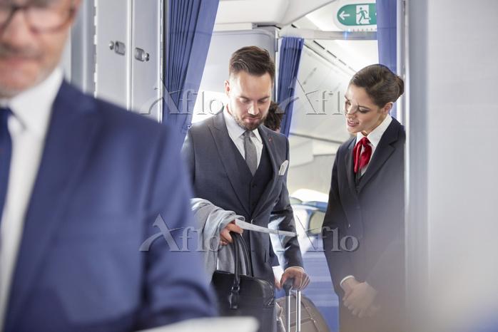 Flight attendant helping busin・・・