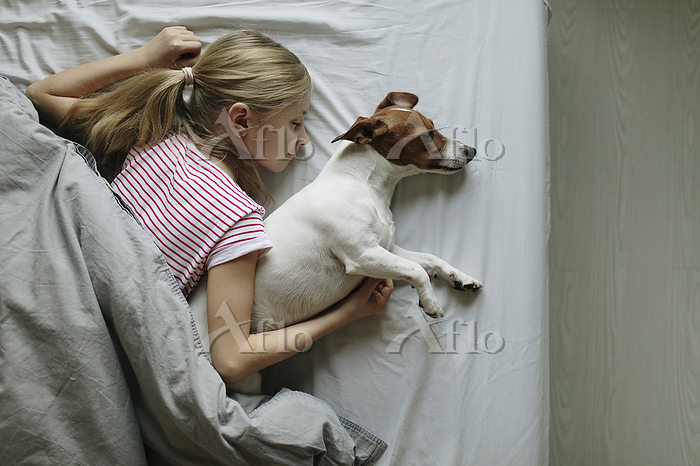 Blond girl lying on bed with h・・・