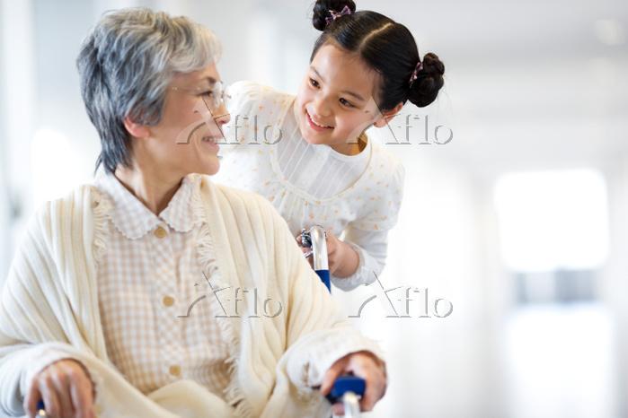 祖母の車椅子を押して話す孫娘