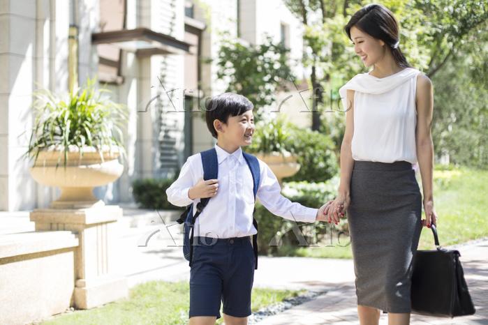 住宅街を笑顔で手を繋ぐ親子