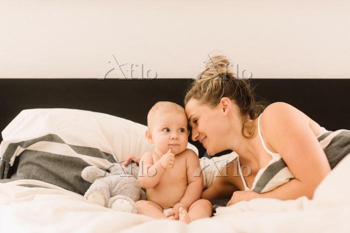 ベッドルームで寛ぐ赤ちゃんと母親