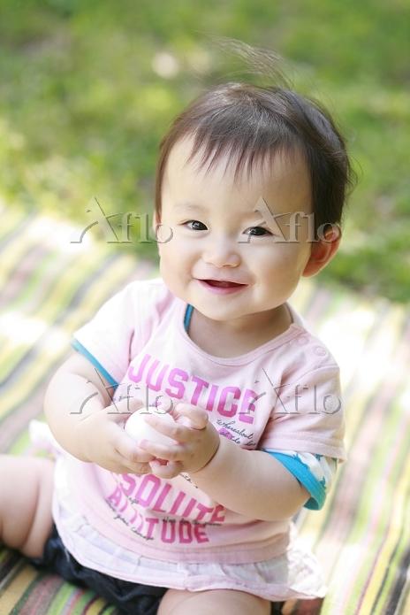 芝生に座る女の日本人の赤ちゃん