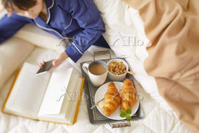 ベッドルームで朝食をとる日本人女性