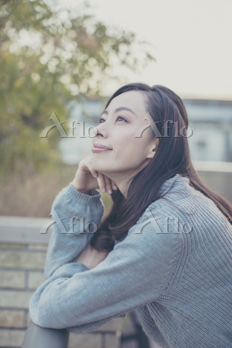 屋上から外を眺める日本人女性