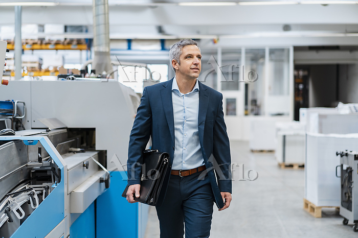 Businessman walking in a facto・・・