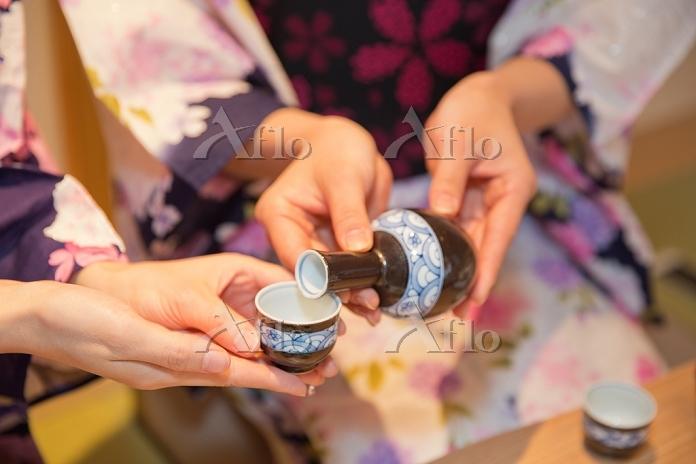 日本酒を注ぐ浴衣の女性手