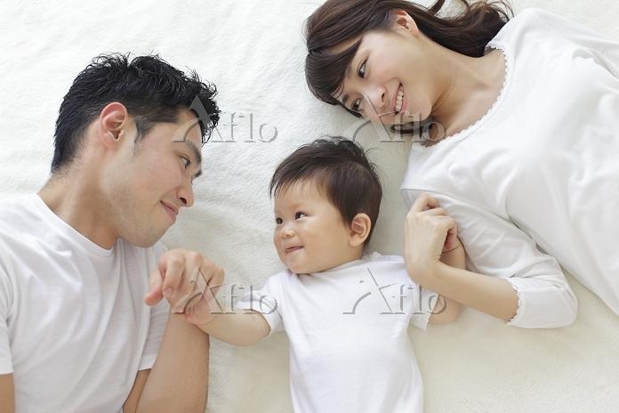 ベッドに寝転ぶ赤ちゃんと両親