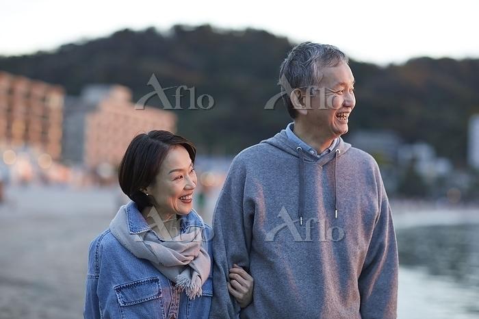 海辺を散歩する日本人シニア夫婦