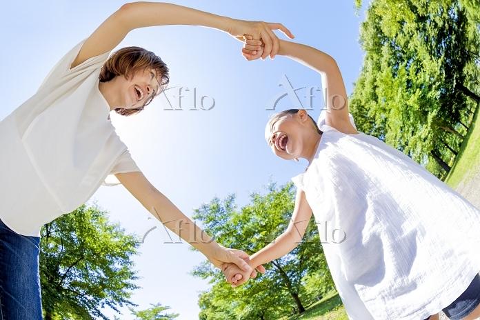 公園で手を繋いで遊ぶ母親と娘