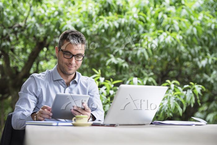 庭でデスクワークをするビジネス男性
