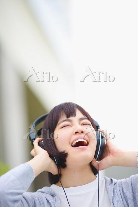 ヘッドフォンで音楽を楽しむ若い日本人女性
