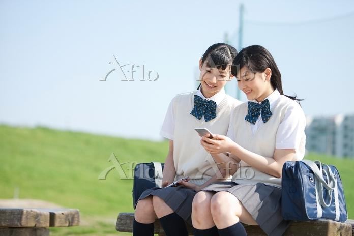 スマートフォンを見ている女子高校生