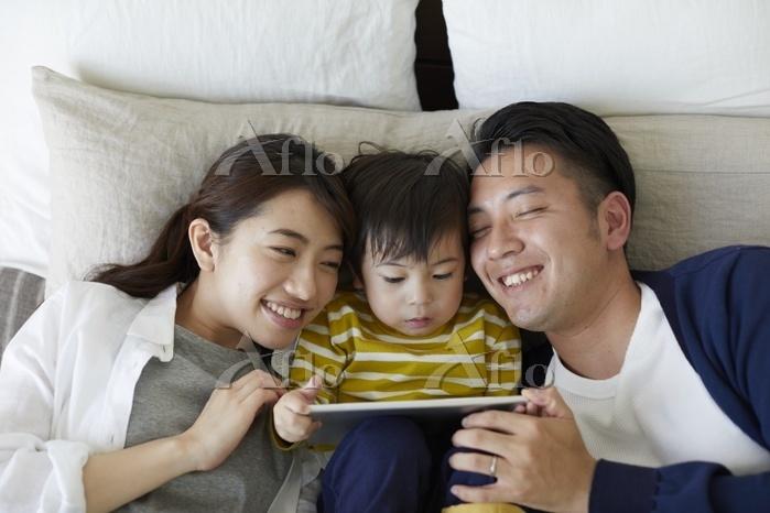 ベッドの上でくつろぐ三人家族