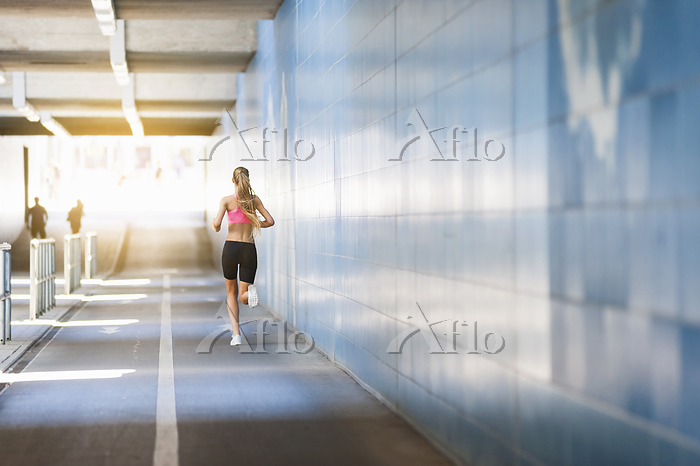 Rear view of female jogger in ・・・