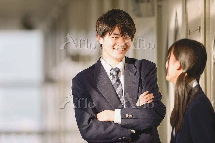 廊下で会話する男女高校生