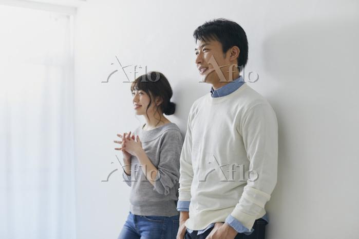 壁に寄りかかるカップル