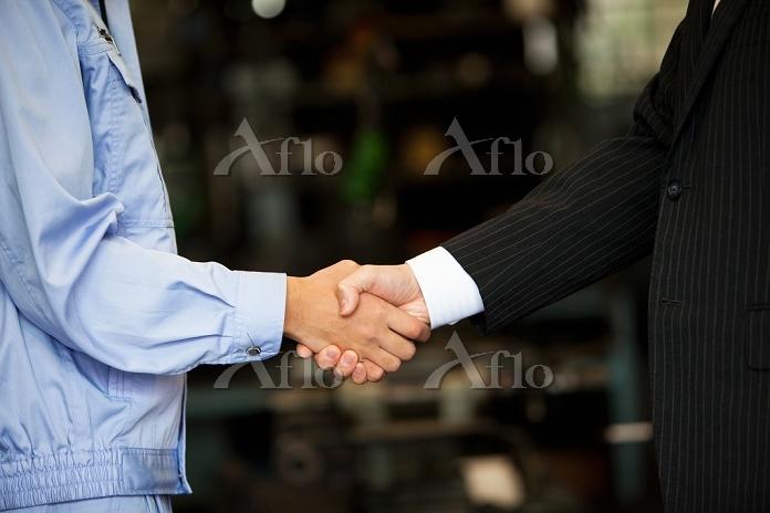 握手する作業員と営業マン
