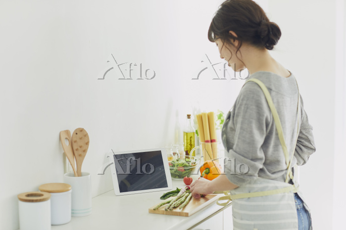 タブレットでレシピを見て料理する女性