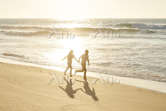 海辺を走る若いカップル