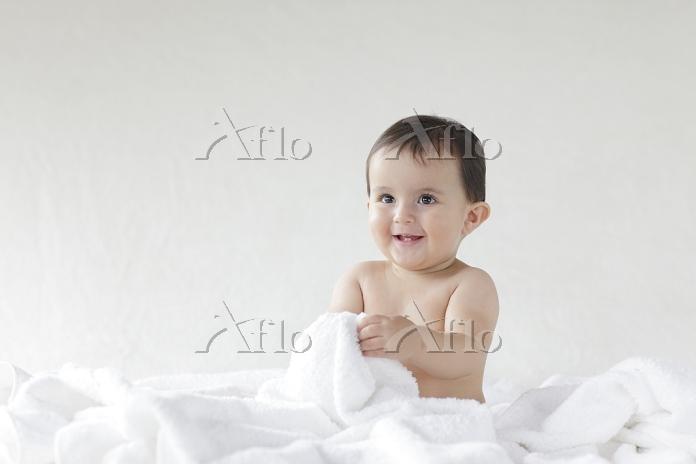 ベッドの上でタオルに包まれる裸の赤ちゃん