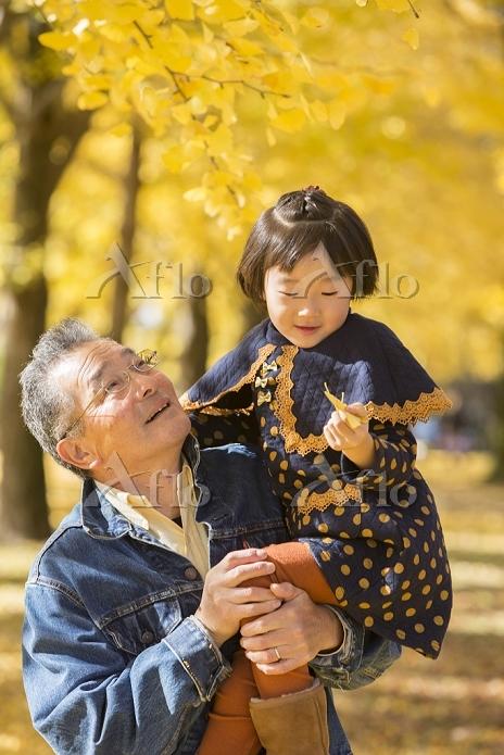 紅葉の銀杏並木のおじいちゃんと孫娘