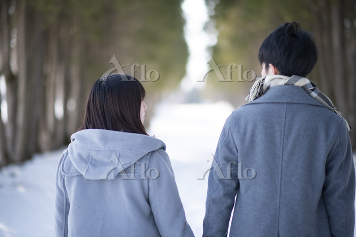 雪道を歩くカップルの後姿