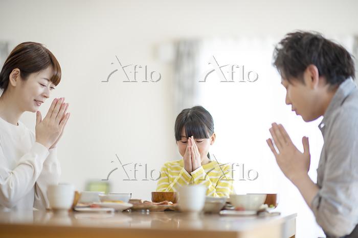 食事を前に手を合わせる家族