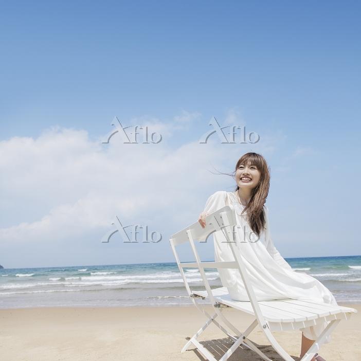 海辺でベンチに座る日本人女性